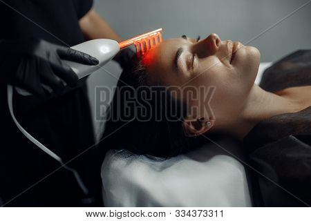 Cosmetologist makes the procedure microcurrent therapy on the hair of a beautiful young woman in cosmetology salon. poster