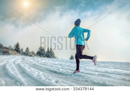 Running woman. Runner on the snow in winter sunny day. Female fitness training outdoors.