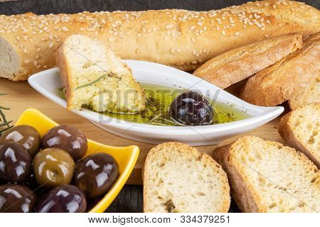 The Bread Dipped In Olive Oil With Olive. Greek Olive Oil Bread Dip. Olive Oil Sauce In White Bowl &