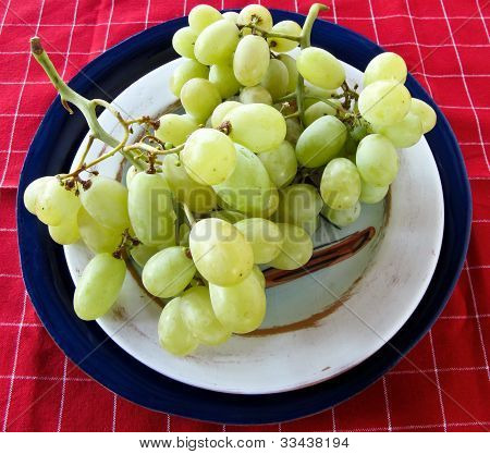 Green Grapes On Pottery And A Red Checked Textile