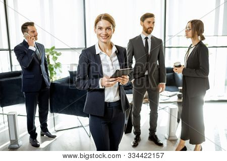 Portrait Of A Beautiful White Collar Busines Woman Standing In Front Of Business Team At The Luxurio