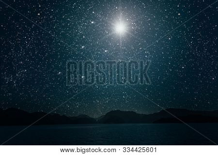 star against a bright night starry sky reflected in the sea. Elements of this image furnished by NASA