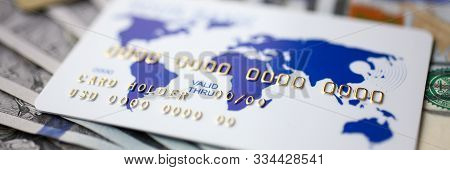 Focus On Credit Card Of Holder Lying On Money Banknotes. World Map Painting On Bankcard. Finance And