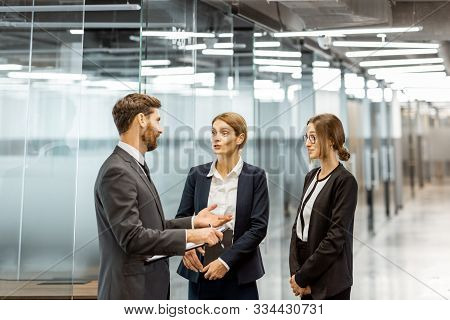 Business People Strictly Dressed In The Suits Meeting In The Hallway Of The Modern Office Building,