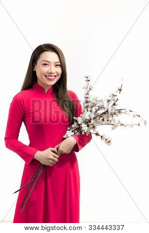 Beautiful Young Woman In Asian Outfit (ao Dai), Holding Flower, Looking At Camera, Smiling.