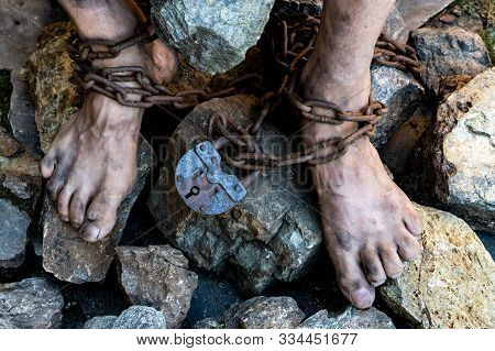 Dirty Slave Legs In Chains Among Stones. Slave In An Attempt To Free Himself. The Symbol Of Slave La