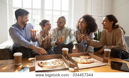 Overjoyed Young Diverse Buddies Eating Ordered Pizza For Home Party.