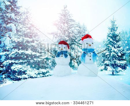 A happy family of snowmen standing in a winter landscape with Christmas trees. Background with snowman.