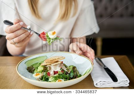 Woman Eats Olivier Salad With Lamb Tongue, Salted Cucumber, Quail Egg. Wooden Table Background. Menu