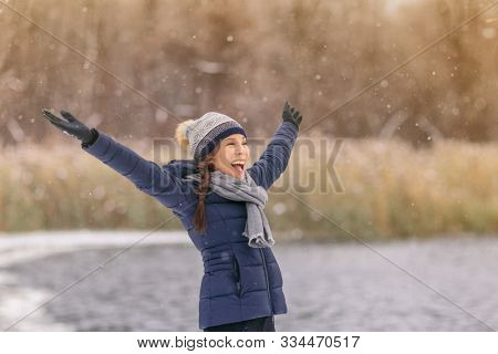 Happy winter snow fun Asian woman playing outside in snowfall enjoying falling snowflakes cold winter weather outdoors in nature forest healthy people lifestyle. Woman wearing hat, gloves ,coat.