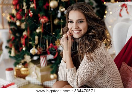 Christmas And New Year Concept - Young Beautiful Woman Sitting In Decorated Living Room With Gift Bo