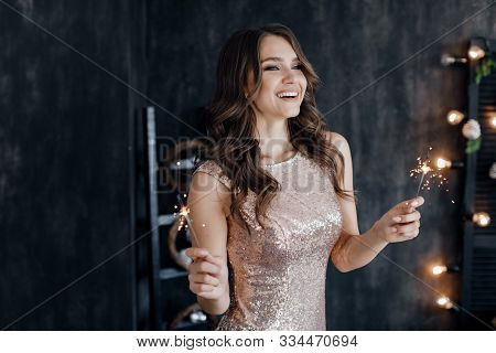 Girl With A Sparkler Near The Christmas Tree. A Cheerful Young Woman With A Cute Smile In A Beige Dr