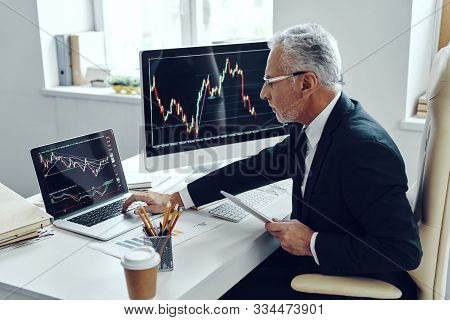 Senior Trader In Elegant Business Suit Using Computer While Working At The Office