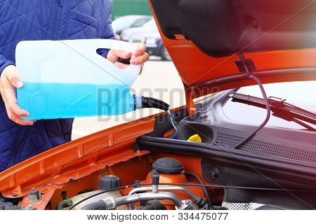 Driver With Blue Washer Fluid In His Hands, Close Up. Car Maintenance Concept. Filling Windshield Wa