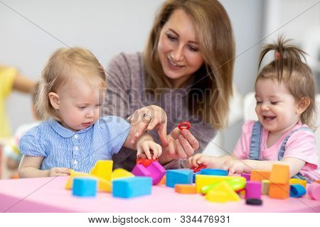 Nursery Kids Play With Educational Toys In Classroom. Kindergarten Teacher Looks After Children