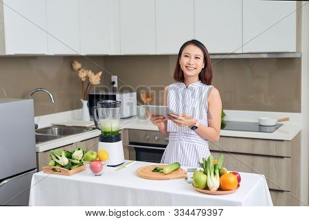Asian Woman Using Tablet To Find Recipe Making Smoothie With Fruit And Vegetable In Kitchen.