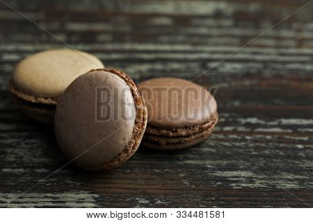 Several Macaroons In Brown Tones On A Wooden Table