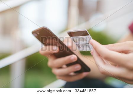 Close-up human hands with mobile phone and credit card. Person holds smartphone and bank card, closeup shot. On foreground male hands hold cell phone and card. Soft focus effect. Outdoors. In the city