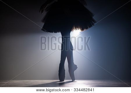 Close Up Silhouette Of Ballerina Legs In Tutu Dress. Ballet Performance On Dark Stage With Floodligh