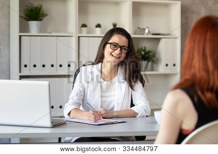 Smilng Manager Talks With Her New Employee And Making Notes. Selective Focus