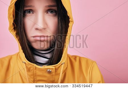 Calm Sad Lady With Green Eyes In A Yellow Raincoat And Striped White And Black Golf Looks Into Frame