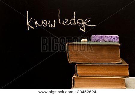 """knowledge"" Written On Blackboard With Old Books"