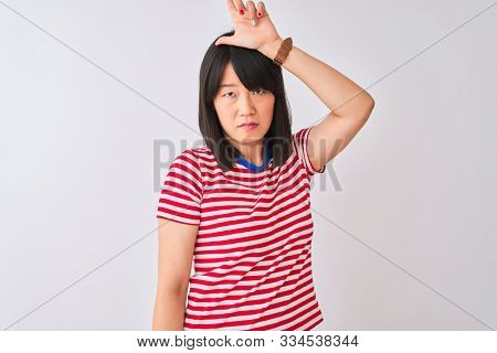 Young beautiful chinese woman wearing red striped t-shirt over isolated white background making fun of people with fingers on forehead doing loser gesture mocking and insulting. poster