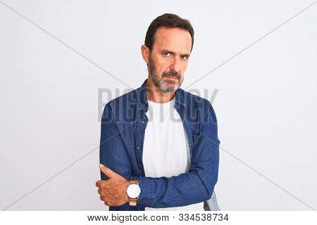 Middle age handsome man wearing blue denim shirt standing over isolated white background skeptic and nervous, disapproving expression on face with crossed arms. Negative person.