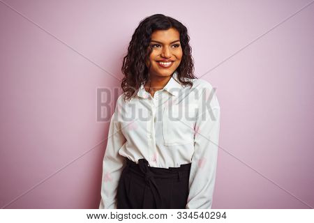 Transsexual transgender businesswoman standing over isolated pink background looking away to side with smile on face, natural expression. Laughing confident.