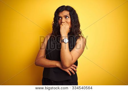 Transsexual transgender elegant businesswoman standing over isolated yellow background looking stressed and nervous with hands on mouth biting nails. Anxiety problem.