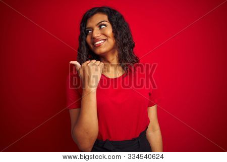 Beautiful transsexual transgender woman wearing t-shirt over isolated red background smiling with happy face looking and pointing to the side with thumb up.