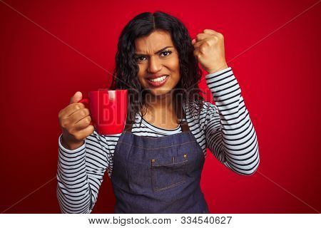 Transsexual transgender barista woman holding cup of coffee over isolated red background annoyed and frustrated shouting with anger, crazy and yelling with raised hand, anger concept