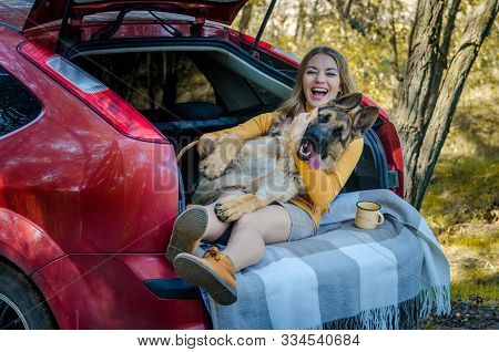 A Happy Caucasian Girl And A German Shepherd Lie In The Trunk Of A Car In Nature. Have Fun, Play And