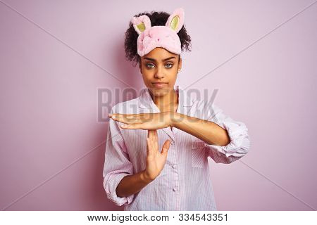 Young african american woman wearing pajama and mask over isolated pink background Doing time out gesture with hands, frustrated and serious face
