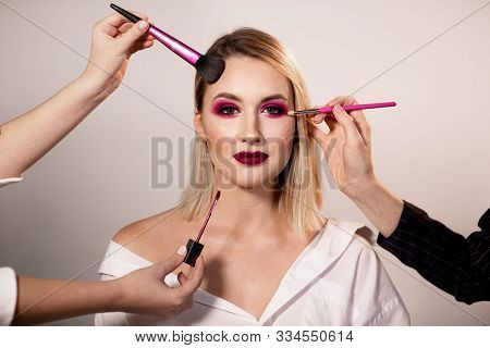 Young Woman With Bright Dark Pink Makeup Posing In Studio Background. Makeup Artists Hands Correct M