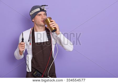Technician Having Rest After Repairing Computer Hardware In Lab, Holding Soldering Iron In Hand And