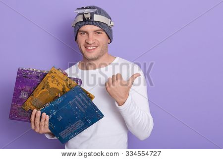 Happy Smiling Radiotrician Wears Casual Outfit With Magnifier On Her Forehead, Holding Three Multico