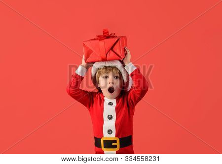 Little Santa Claus Gifting Gift. Cute Boy In Santa Hat. Christmas Children. Little Kids Celebrating