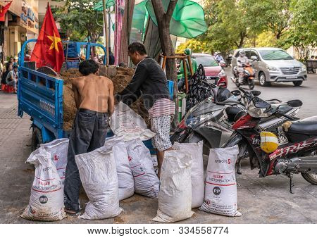 Ho Chi Minh City, Vietnam - March 12, 2019: Downtown Street Scenery. 2 Workers Fill Manually White P
