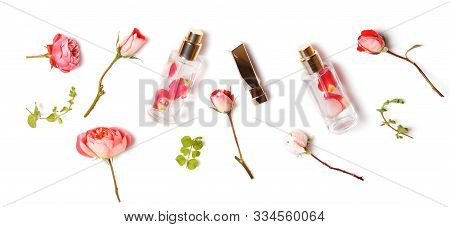 Essential Aroma Oil With Roses On Wooden Background. Beauty Workspace With Roses, Cosmetics. Top Vie