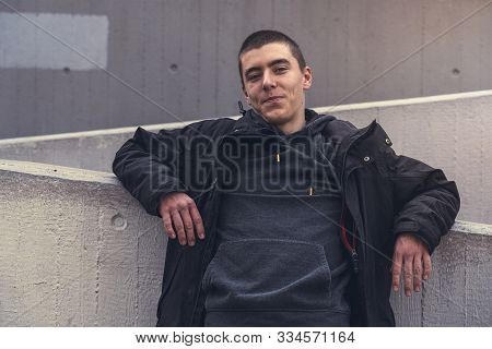 Portrait Of A Smiling Young Man Leaning Against A Concrete Wall