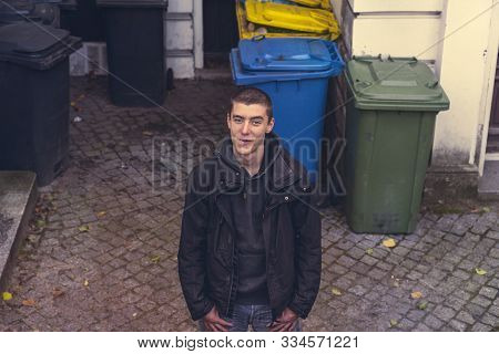 Portrait Of A Casual Young Man Standing In Front Of Garbage Cans