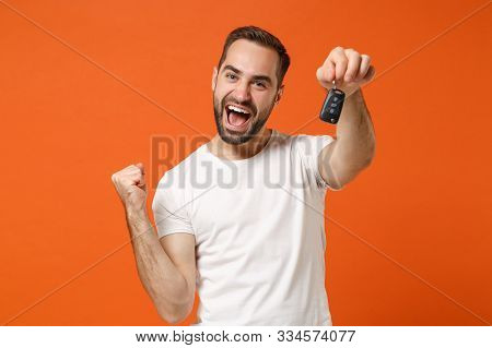 Joyful Young Man In Casual White T-shirt Posing Isolated On Orange Background Studio Portrait. Peopl