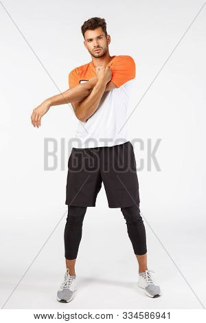Motivation, fitness and bodybuilding concept. Full-length motivated good-looking sportsman stretching arms, warm-up before starting exercises, ease tension in muscles, standing white background poster