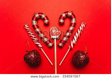 Christmas Sweets On A Red Background: Gingerbread In The Shape Of Mittens, Lollypops, Apples. Festiv