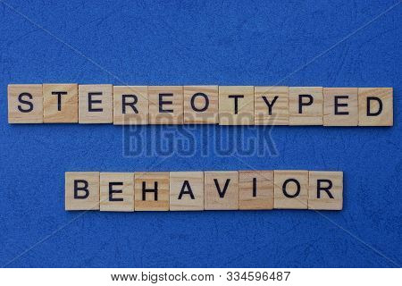 Word Stereotyped Behavior Made From Brown Wooden Letters Lies On A Blue Table