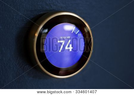 Smart Thermostat Against A Blue Wall. Smart Thermostat On Dark Blue Wall. Small Reflection Present