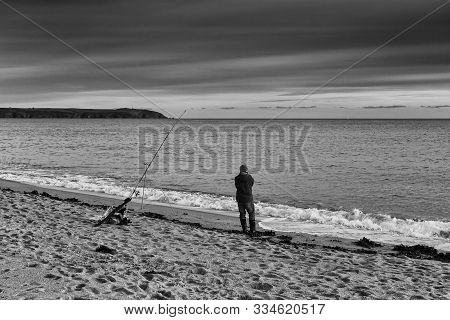 A Lonely Fisherman Is Looking At The Sea During Sunset In St. Austell, Cornwall, United Kingdom.