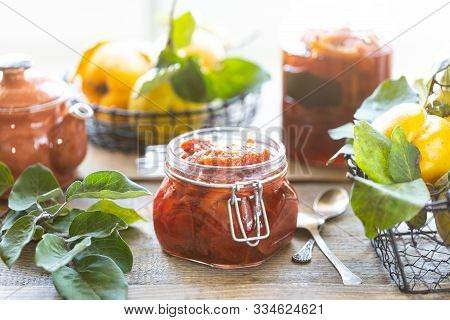 Homemade Quince Jam In A Glass Jar On An Old Wooden Background. Fresh Fruits And Leaves Of Eggs Arou
