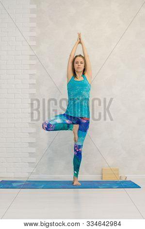 Portrait Of Beautiful Young Woman Practicing Yoga Indoor. Girl In Blue Sportswear Practice Vrikshasa